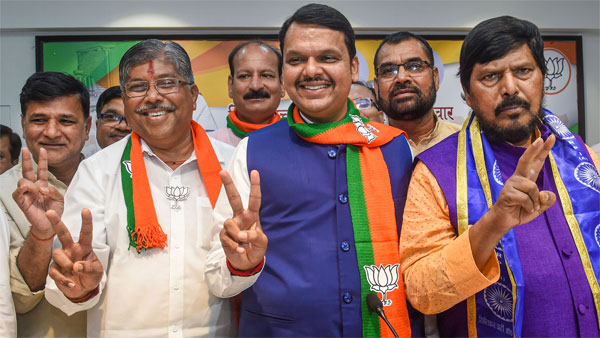 Maharashtra Chief Minister Devendra Fadnavis, State BJP president Chandrakant Patil and RPI chief Ramdas Athawale flash victory signs as they celebrate their win in Maharashtra Assembly elections, in Mumbai