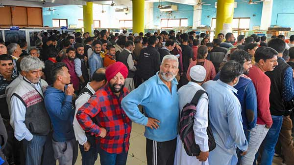 People stand in a queue at a telecom office to restore their mobile phones, in Srinagar