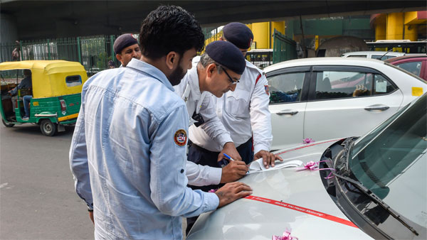 Traffic policemen impose penalty on a traffic offender for riding a vehicle with a number plate ending with an odd digit during the Odd-Even scheme, in New Delhi