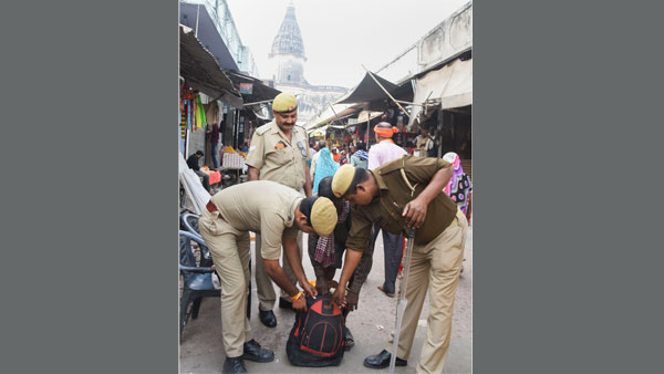 Police personnel check a bag of a passer-by in Ayodhya