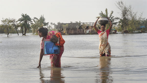 Villagers make through a flooded area following cyclone Bulbul