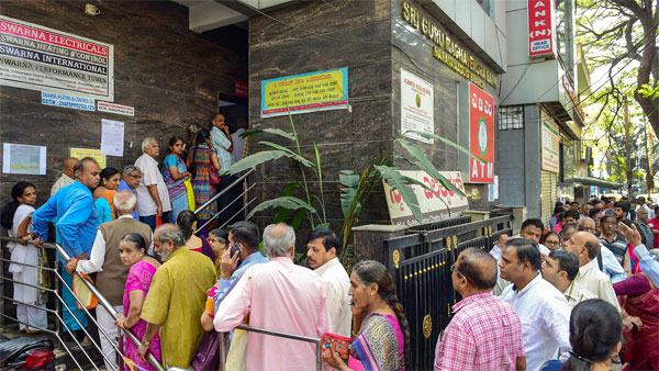Depositors stand in queue to withdraw money from Sri Guru Raghavendra Sahakara Bank in Bengaluru, Tuesday, Jan.14, 2020. The Reserve Bank of India (RBI) has curbed Sri Guru Raghavendra Sahakara bank from doing business with immediate effect for alleged irregularities in transactions.