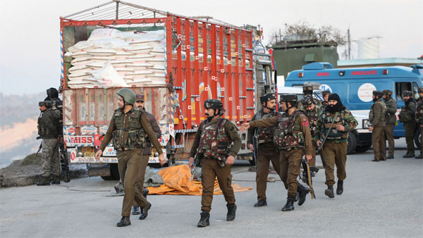 Security personnel walk past the Srinagar-bound truck in which a group of 3-4 terrorists were travelling, on the Jammu-Srinagar national highway