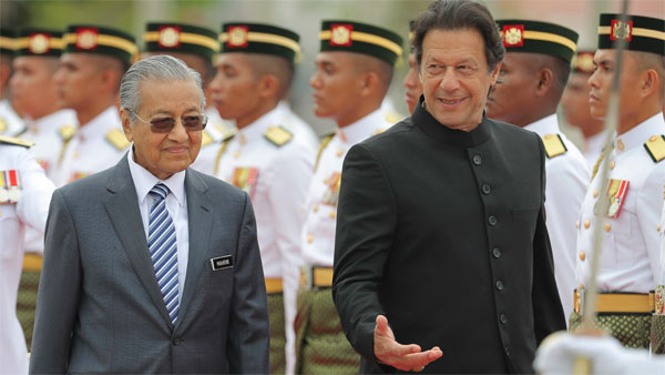 Pakistans Prime Minister Imran Khan, right, talks with Malaysias Prime Minister Mahathir Mohamad