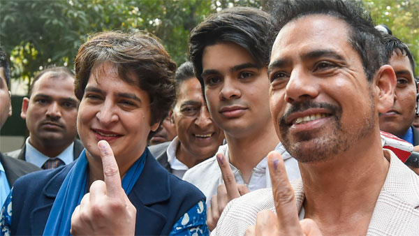 Priyanka Gandhi Vadra along with her husband Robert Vadra (R) and son Raihan Vadra (C), who voted for the first time, show their finger marked with indelible ink after casting vote during the Delhi Assembly elections