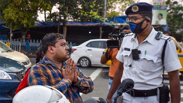 A biker apologizes after being stopped by a police personnel during lockdown in the wake of coronavirus pandemic, in Kolkata