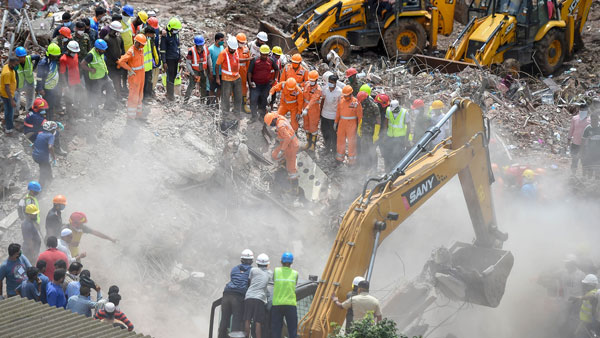 Rescue personnel sift through the rubble in search of survivors at the site where a five-storey apartment building collapsed, at Mahad in Raigad district