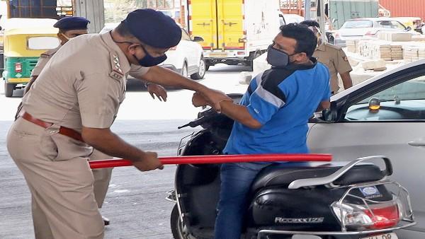 Lockdown-like restrictions in Karnataka kick in; Policemen wielding lathis on violators in Bengaluru