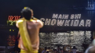 A Priest Is Seen In The Foreground As BJP Party Symbol And Election Slogan Illuminates
