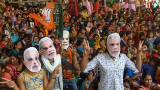 BJP supporters wearing masks of Prime Minister Narendra Modi flash victory signs