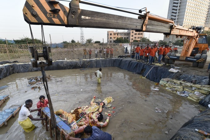 Devotees Immerse An Idol Of Goddess Durga Using A Crane At A Pond In Mayur Vihar, New Delhi